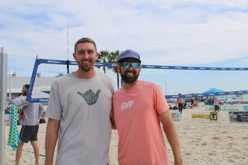 Two men looking at the camera on a beach in front of a volleyball net.
