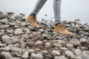 Brown boots walking on stones near a body of water