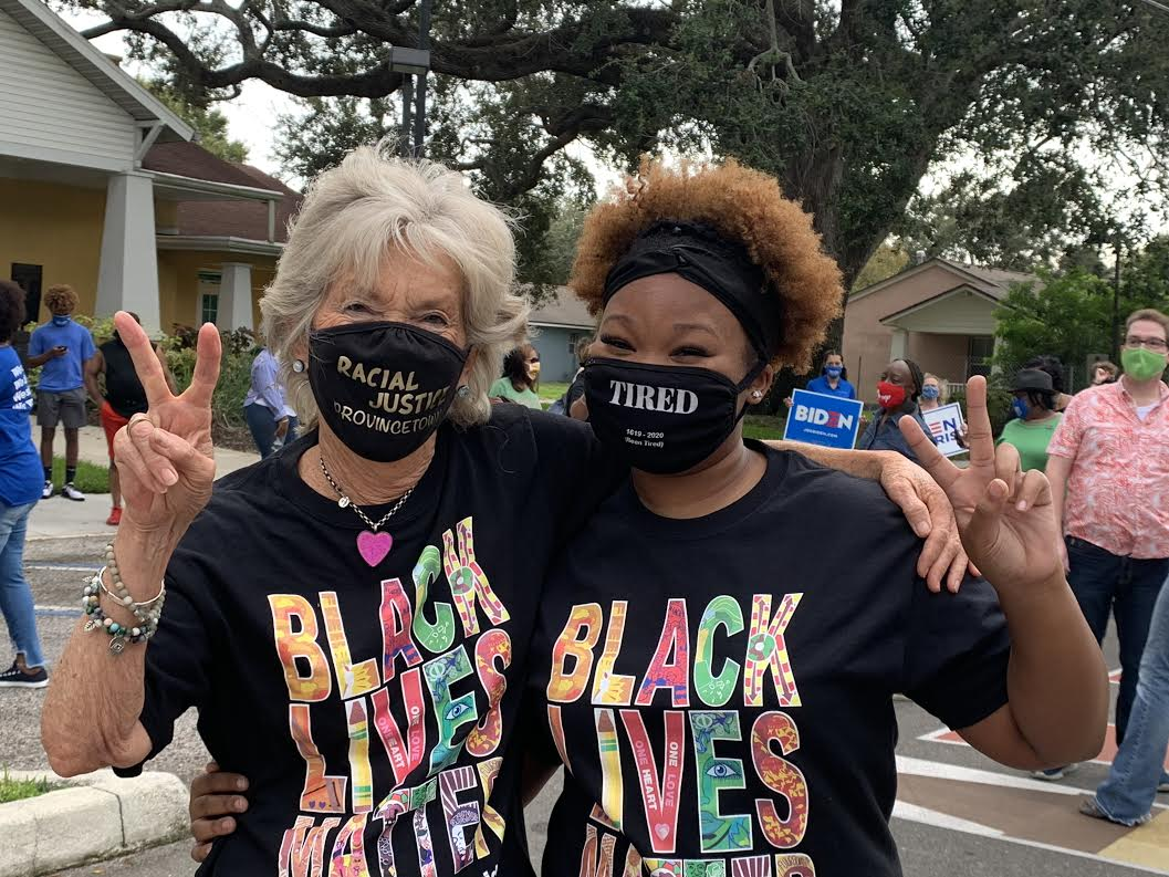 Two women with face masks and Black Lives Matter T-Shirts pose for the camera.