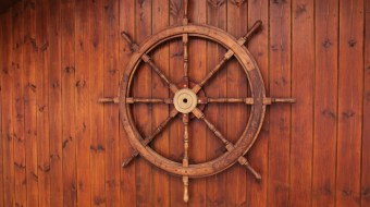 A brown wooden boat steering wheel on a wooden wall