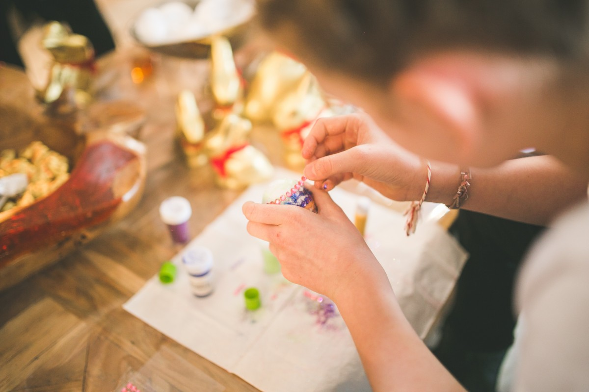 Girl creating a craft with clue and paint, just her hands are shown