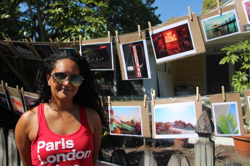 A woman in a red top stands outside next to a display of art.