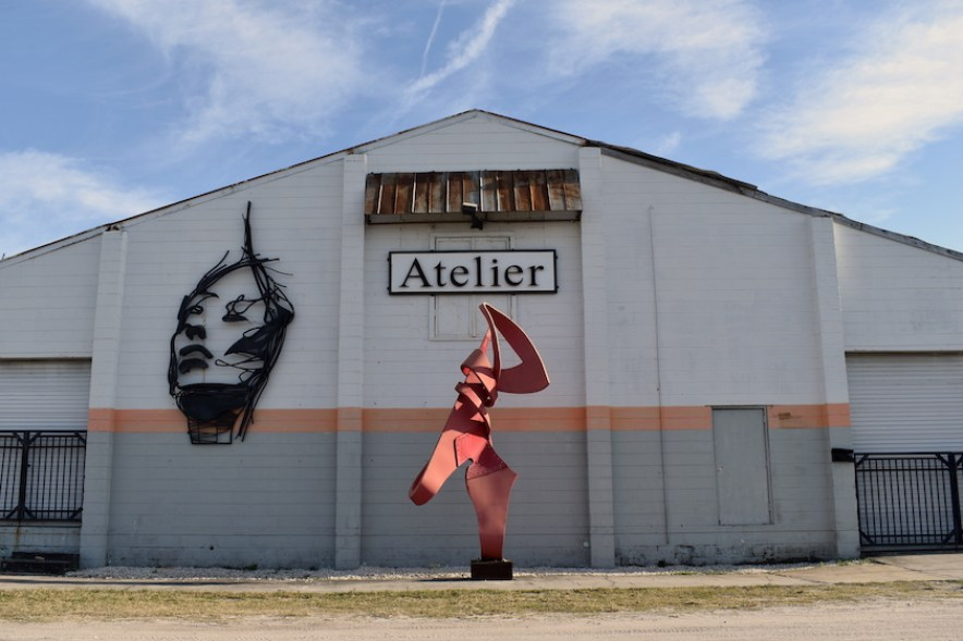 """A warehouse building with a red abstract sculpture and a sign that reads """"Atelier"""""""