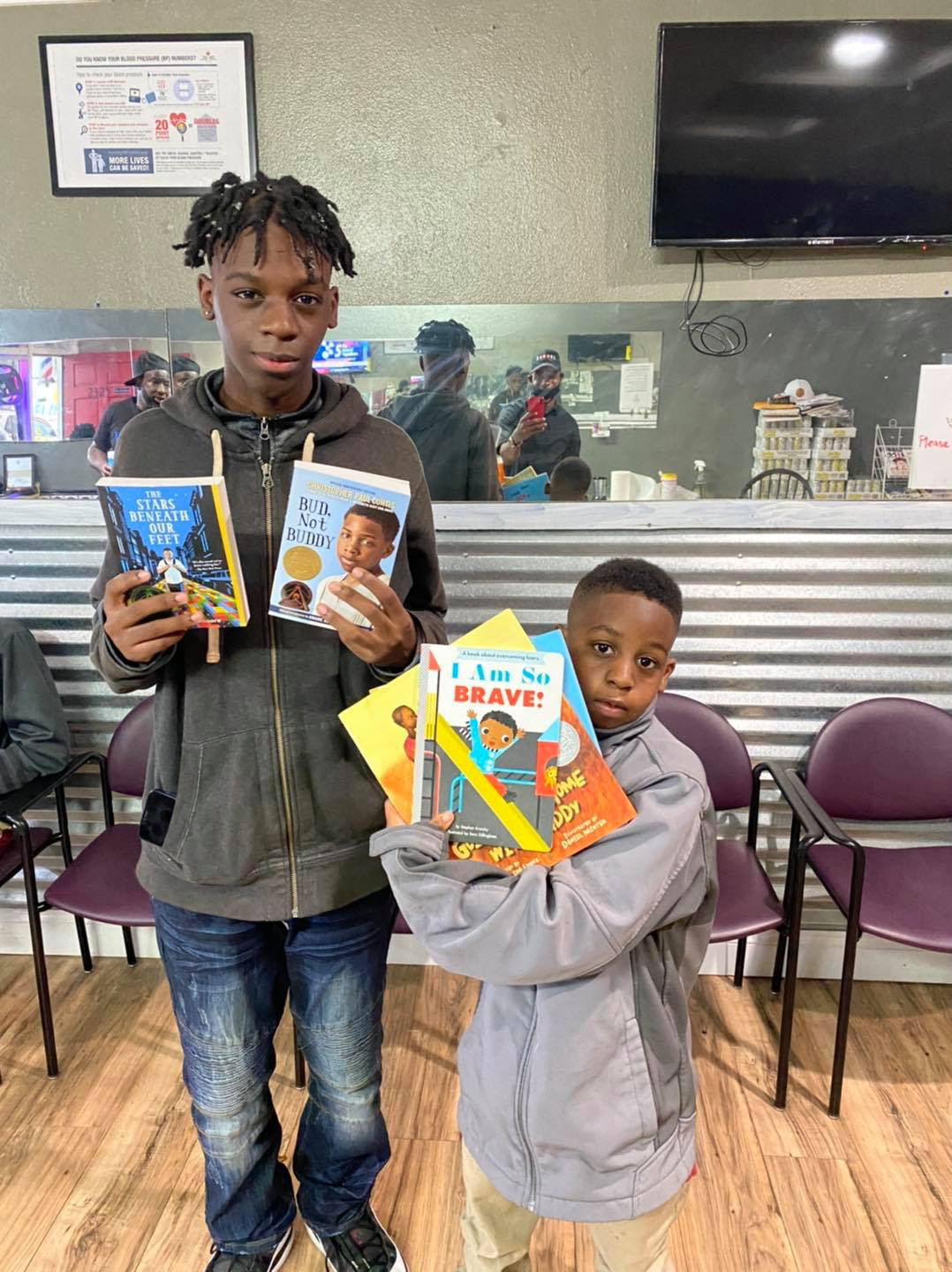 Two boys holding up multiple copies of books
