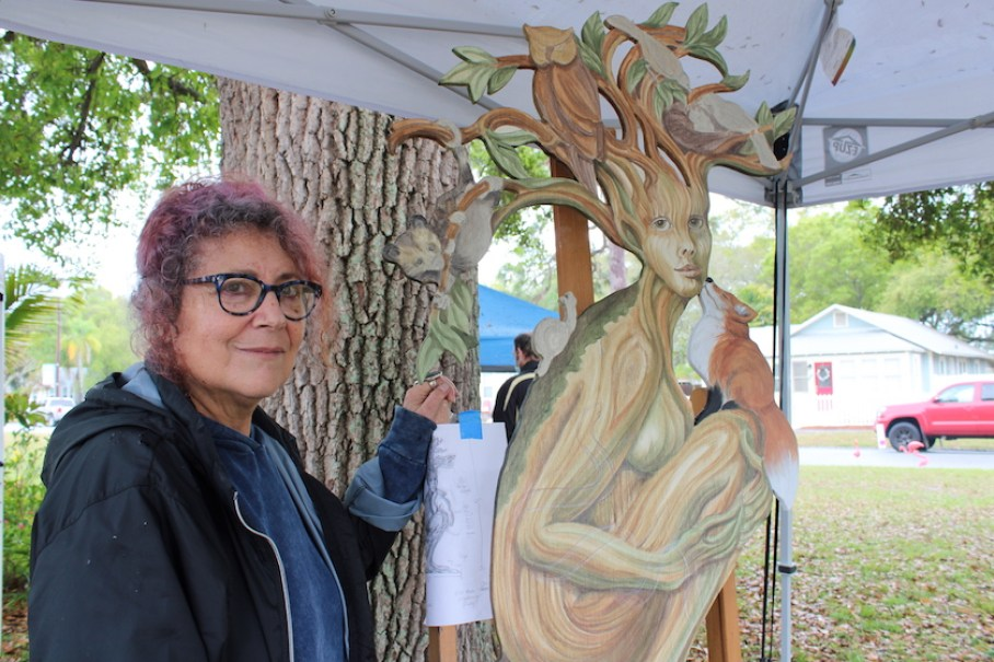 A woman with glasses standing outside under a tent next to a piece of art, a woman in a tree trunk