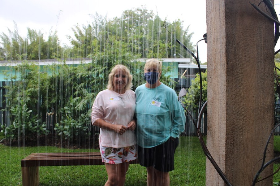 Two women standing outside on the other side of a garden water feature