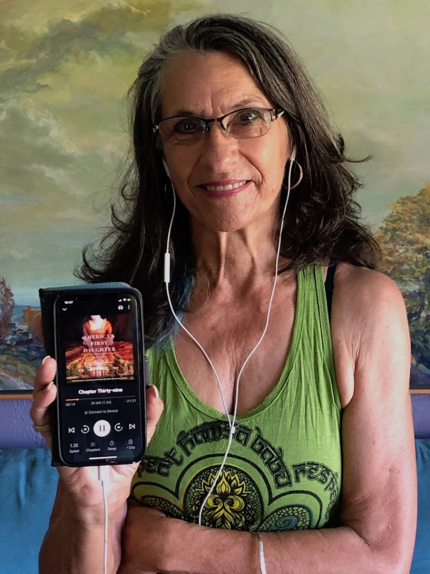 Photo of a woman in a green tank top with white headphones holding up a phone with an audiobook on it.