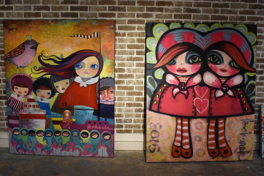 Two colorful canvases of pop art ladies against a brick wall.
