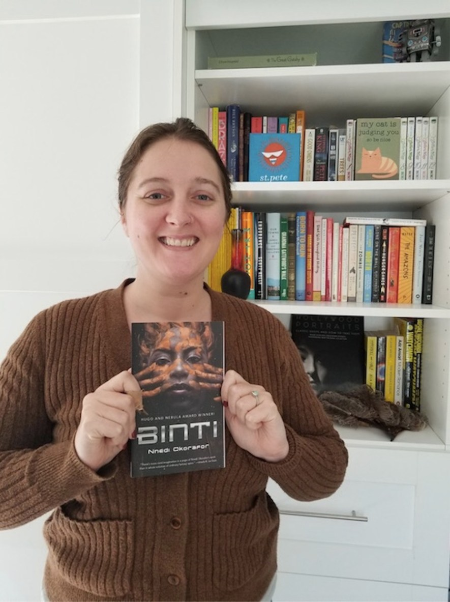 """A woman standing in front of a book shelf holding up a book titled """"Binti"""" by Nnedi Okorafor"""