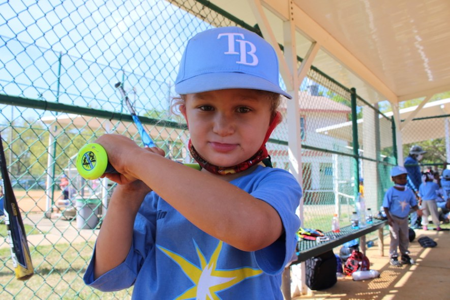 A little kid in a baseball outfit holding a bat