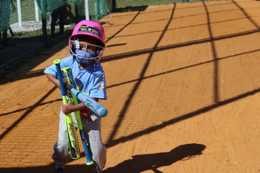 A little kid in a baseball outfit holding bats
