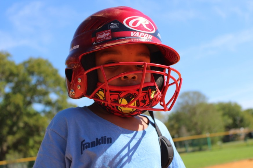 A kid in a red baseball helmet with face cage