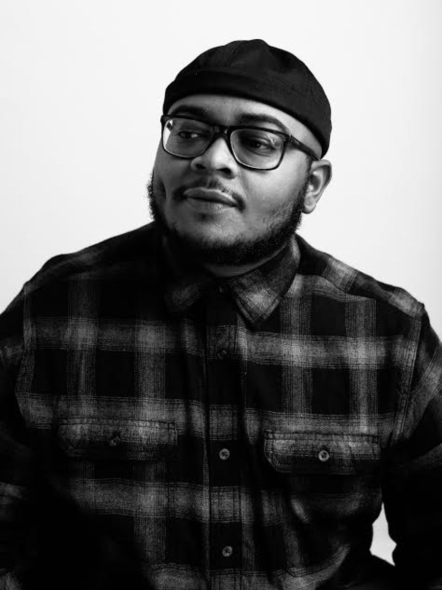 A black and white photo of a man in head cap, glasses and plaid shirt