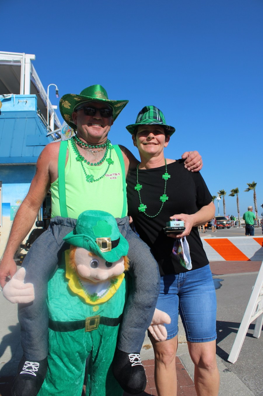 Two people pose on the street in St. Patrick's Day costumes
