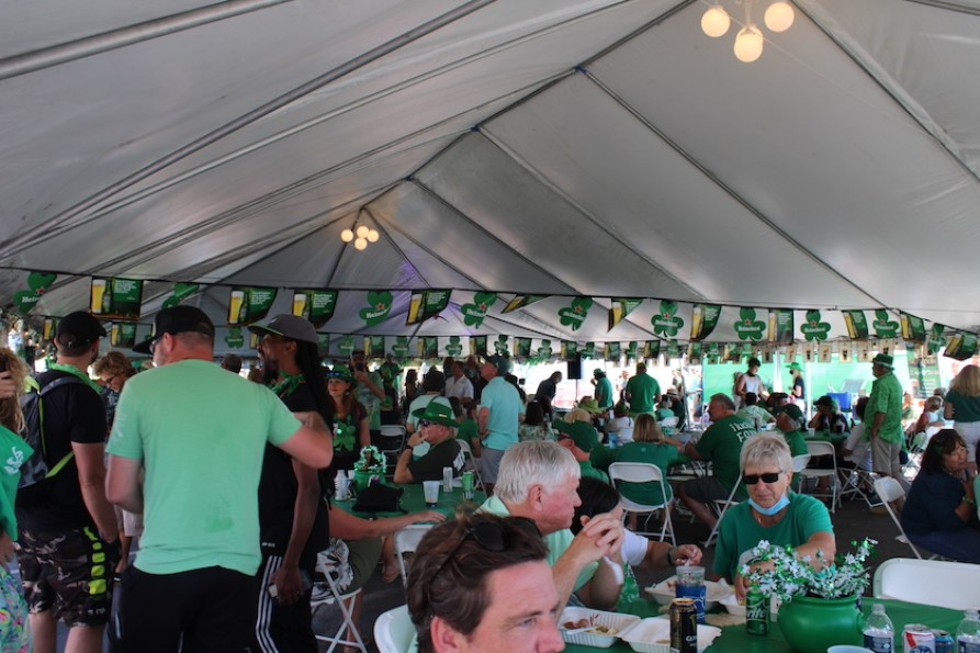 A crowd under a tent at a St. Patrick's Day event.