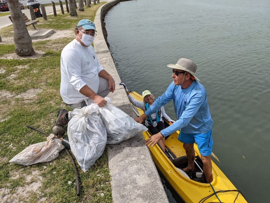 A man and a woman in a yellow kayak in the water dropping bags of trash to a man on the seawall