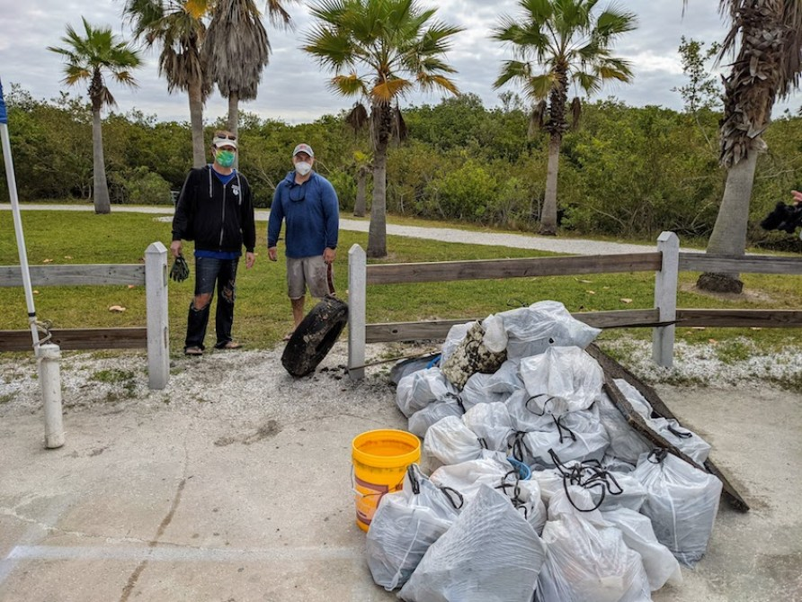 Two people in Face masks outdoors with an old car tire standing next to many piles of trash.