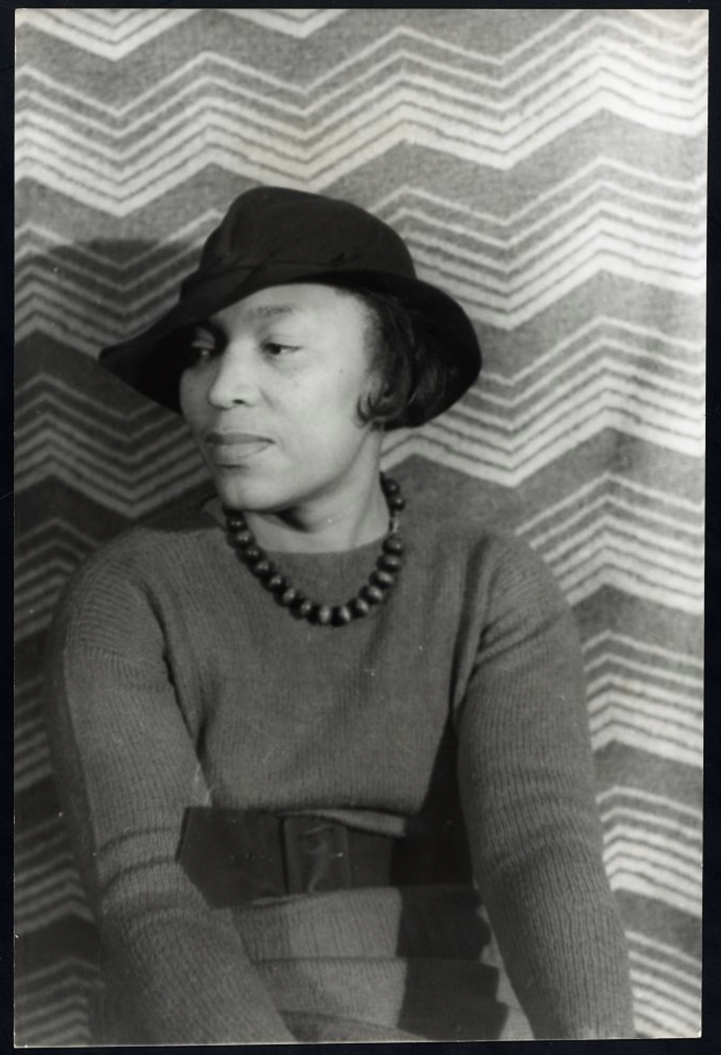 A black and white image of a woman in a black hat looking to the side.