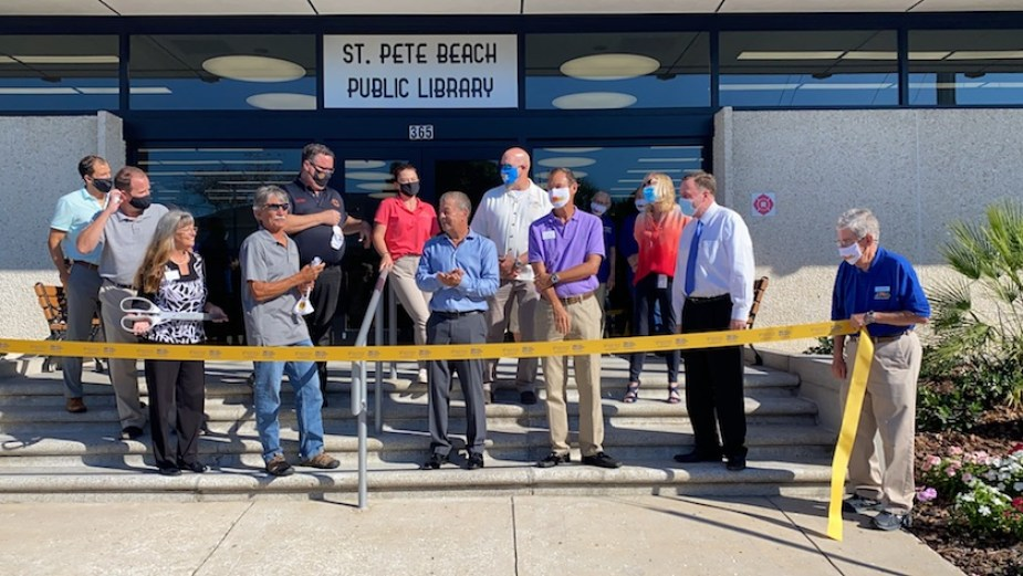 """A group of people standing behind a yellow ribbon outside a building with a sign that reads """"St. Pete Beach Public Library"""""""