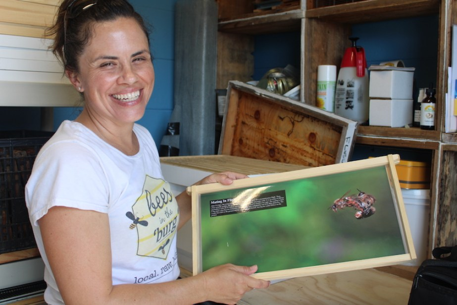 A woman smiling at the camera holding up a panel with info about bees