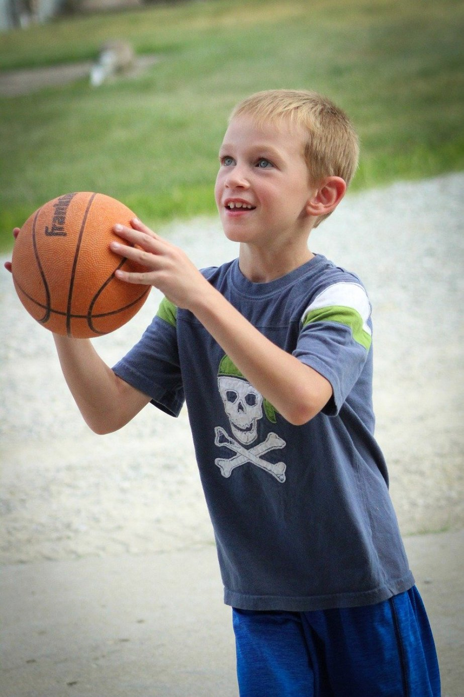 A young boy in shorts and t-shirt getting ready to shoot a basketball.