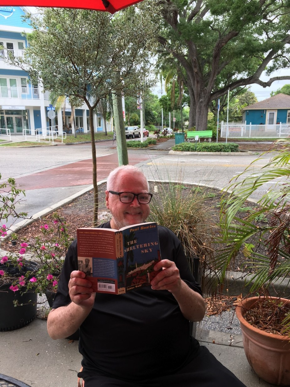 """A man sitting on an outdoor patio holding up a book titled """"The Sheltering Sky"""""""