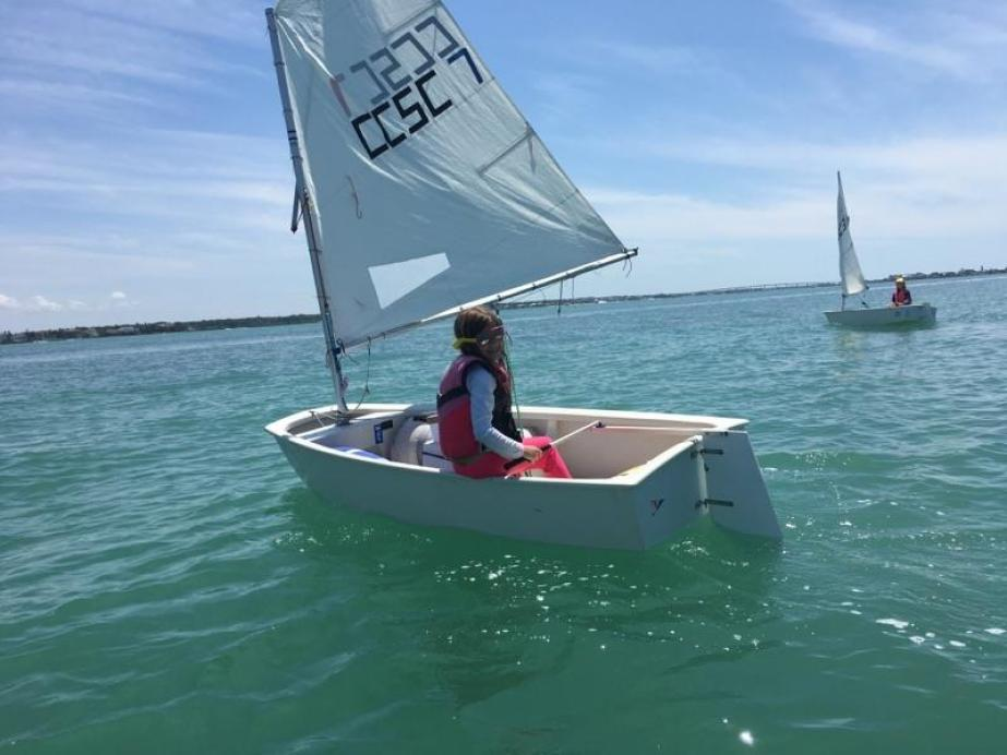 A child sailing on a small boat in blue/green water.