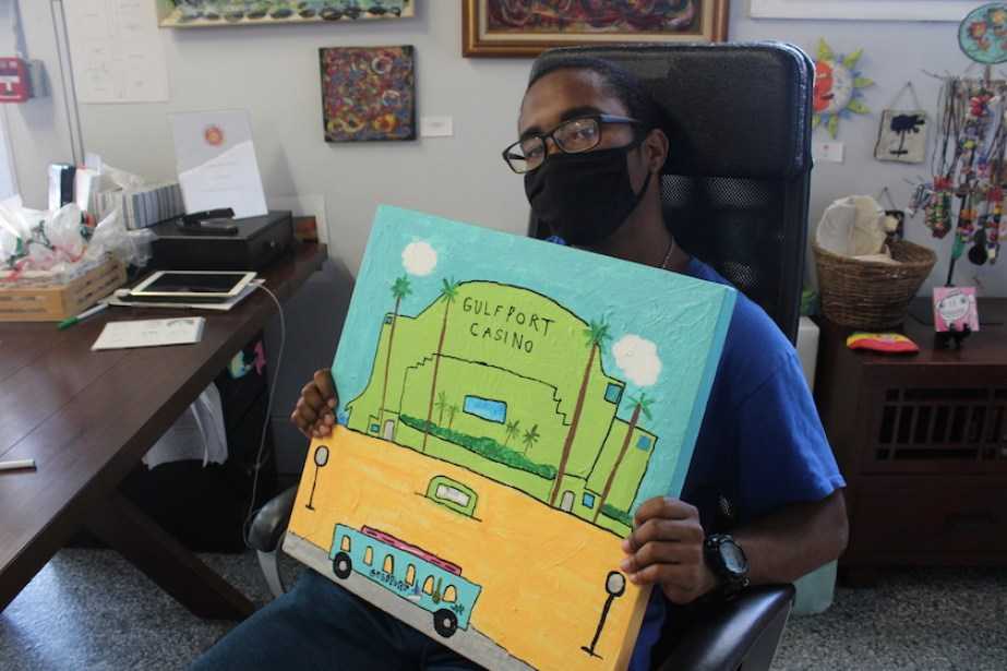 A photo of a young man in face mask holding up a painting of the Gulfport Casino.
