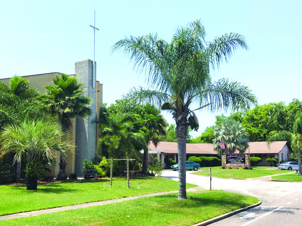A photo of a church property with a cross on the steeple and a palm tree in the foreground.