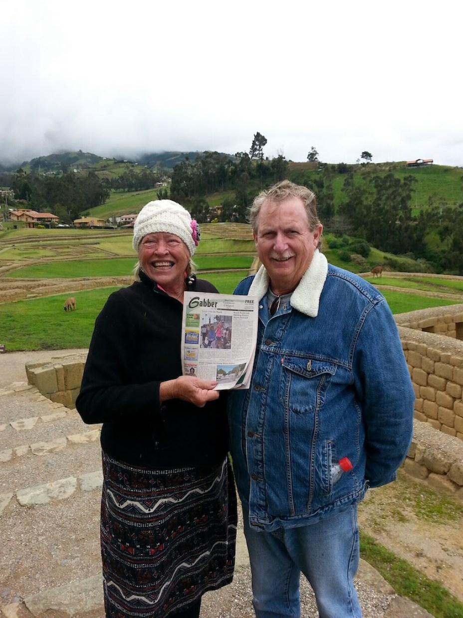 A mand and a woman in warm clothes smiling at the camera holding a Gabber Newspaper outdoors.
