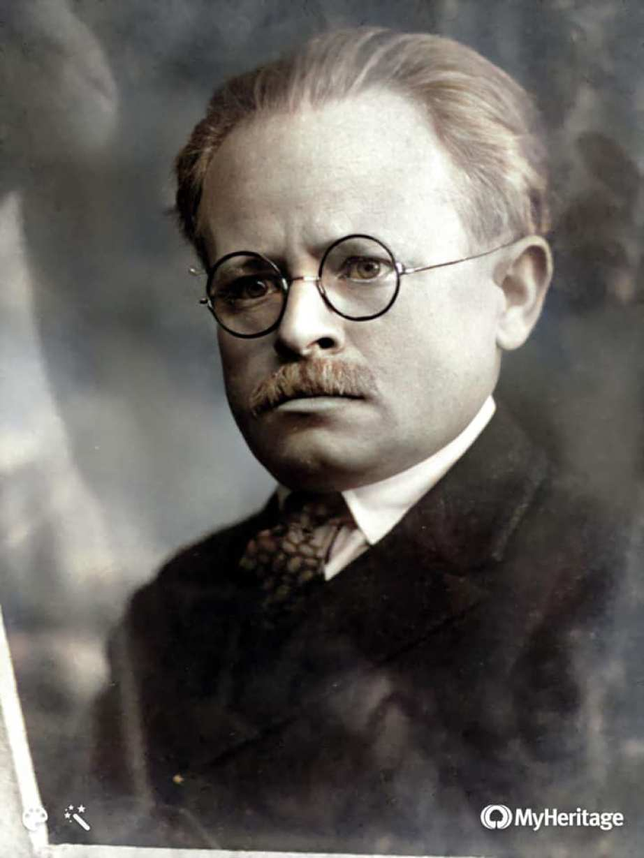 An old photo portrait of a man in a suit with glasses and a mustache.
