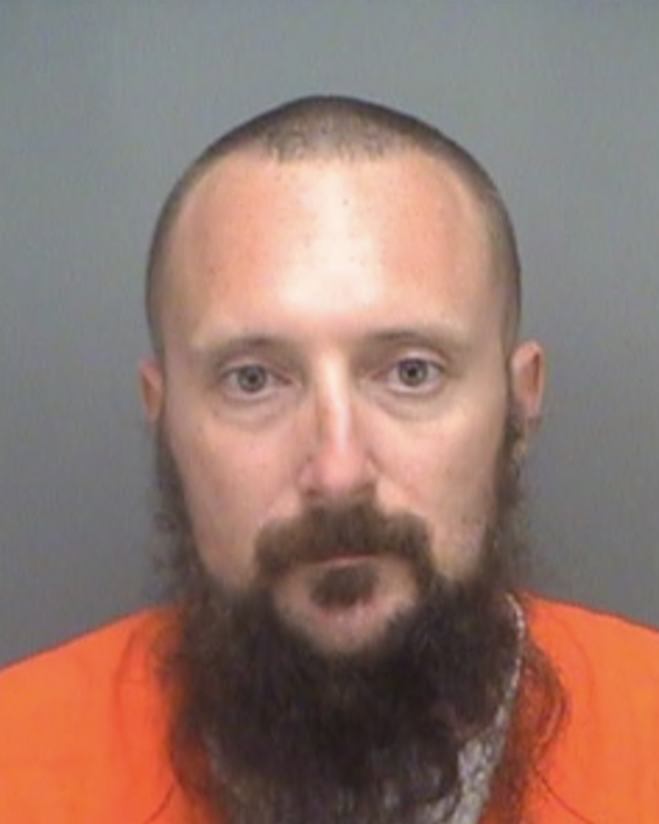 A mug shot of a man with a shaved head and a long brown beard, dressed in an orange jumpsuit.