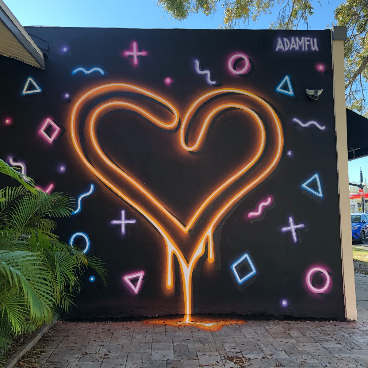 A black mural on the side of a building with a neon-look heart and symbols spray painted on it.