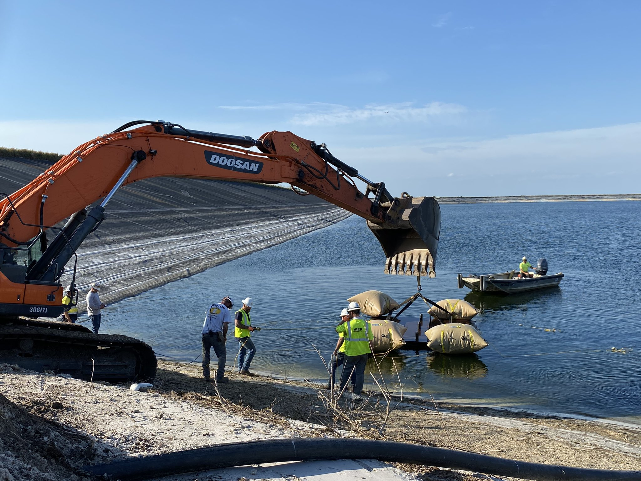 People and a large digger claw putting submersibles into a large reservoir