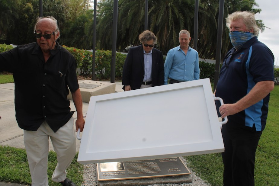 Two men removing the cover of a memorial plaque while two men watch.