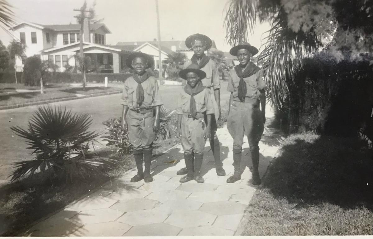 A black and white photo of boys in old fashioned Scouting uniforms.