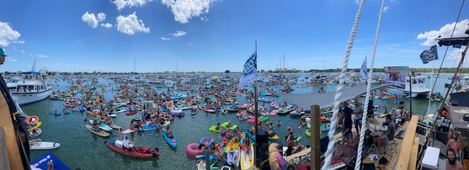 A wide angle photo of hundreds of boaters and kayaks in the water at a music festival.