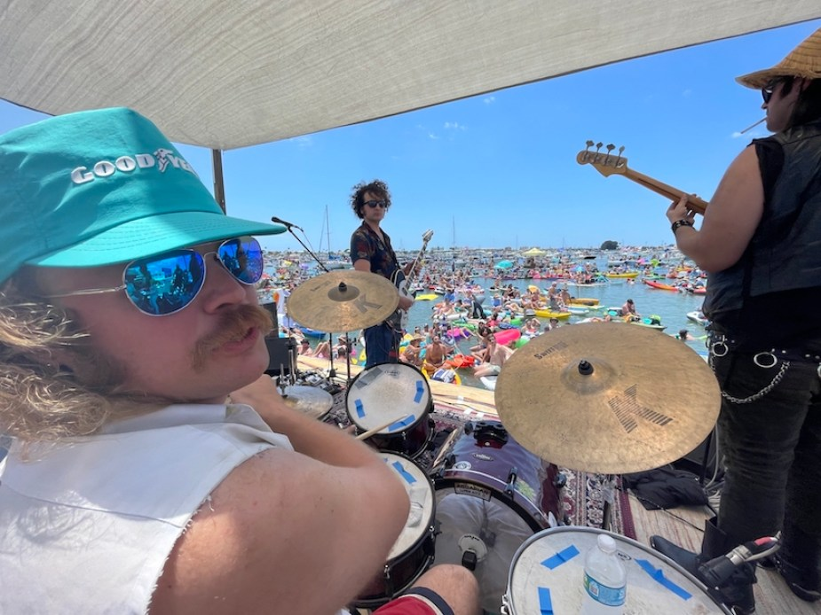 A man in a blue hat and sunglasses playing a drum kit on a stage in the water