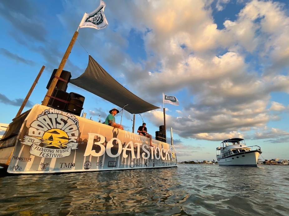 """A stage in the water with the a banner that reads """"Boatstock"""""""