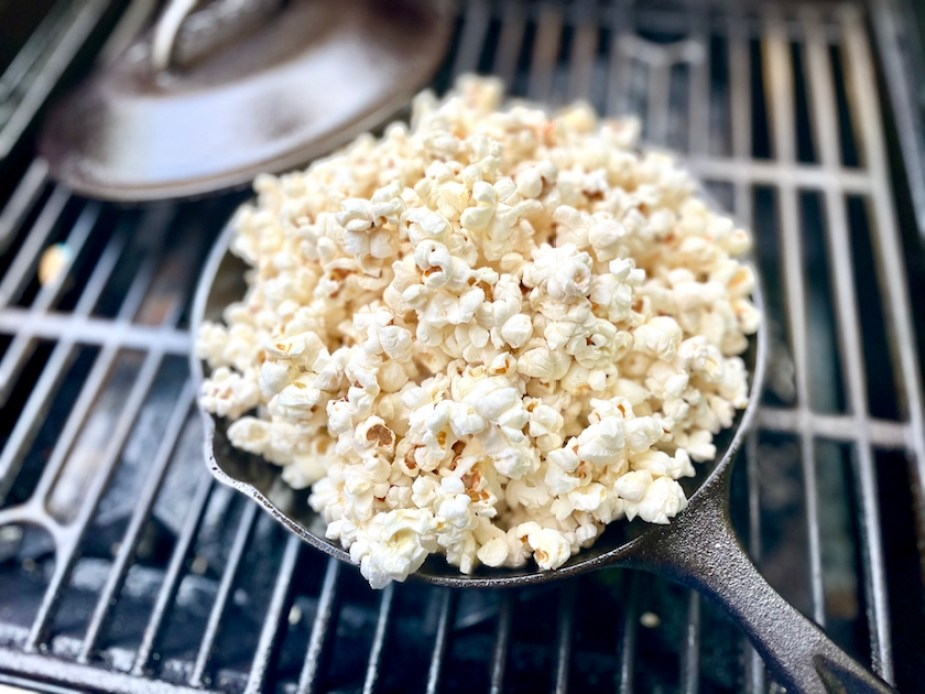 A cast iron skillet full of popped popcorn on a grill.