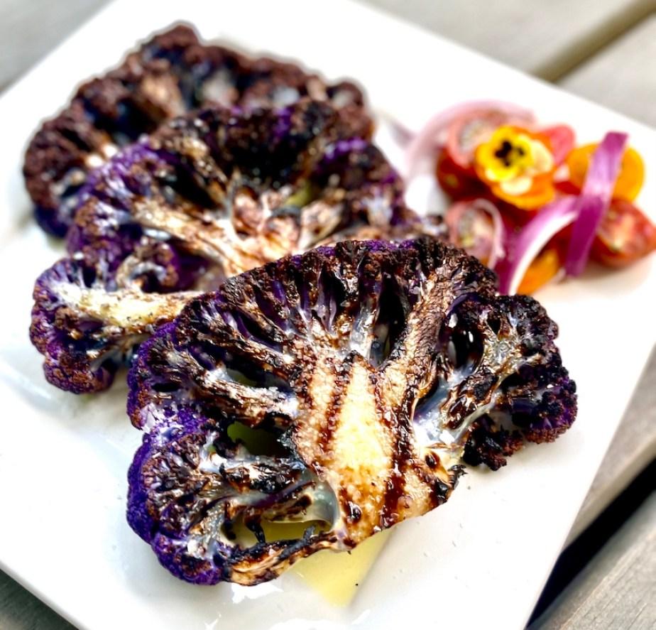 A plate of grilled purple cauliflower steaks.