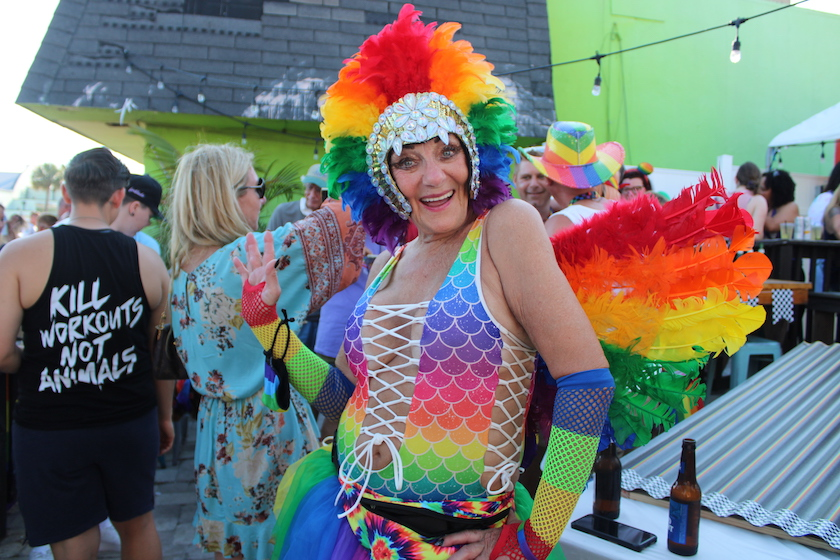 A woman dressed in full rainbow costume with wings and head gear poses for the camera.