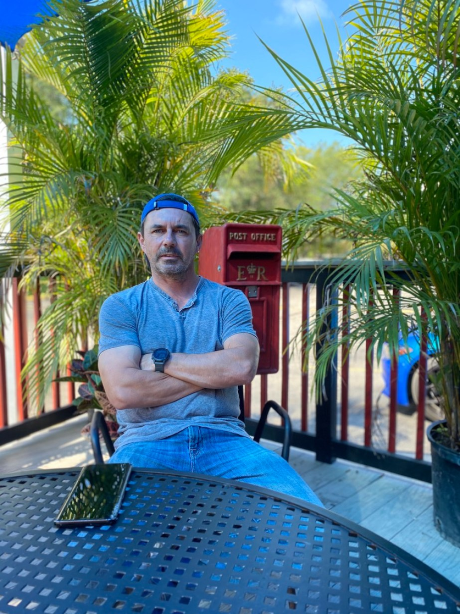 A man in a blue t-shirt sitting at an outdoor table with palm trees and a red mailbox behind him.