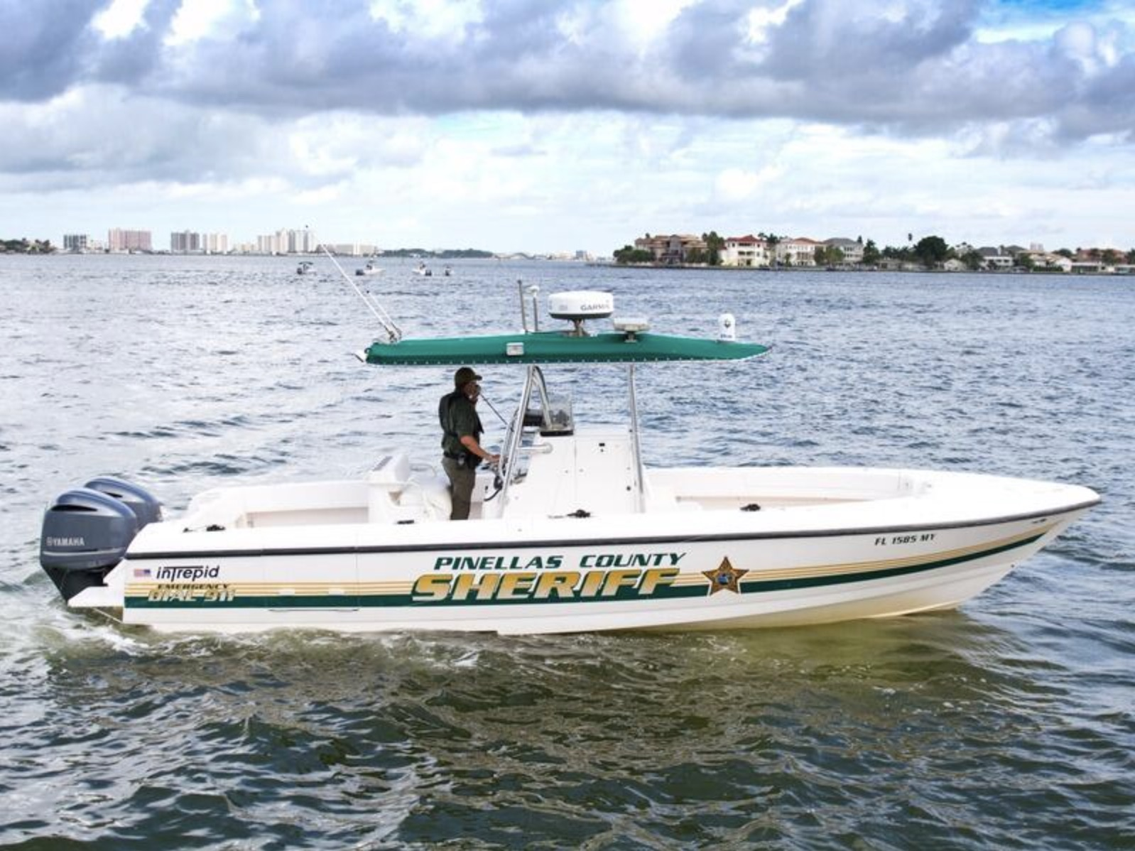 A Pinellas County Sheriff's Marine Unit boat with one driver out on the water with houses in the background.