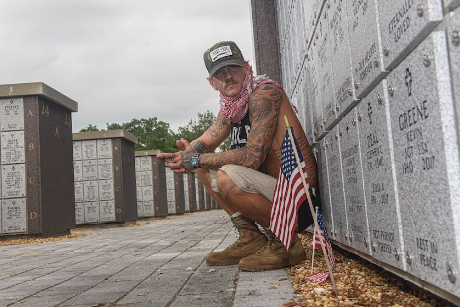A man sitting at a cemetery crypt next to a small American flag.