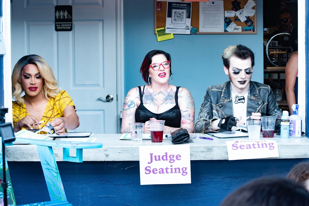 """People in costume sitting at a table with a sign that reads """"Judge Seating"""""""