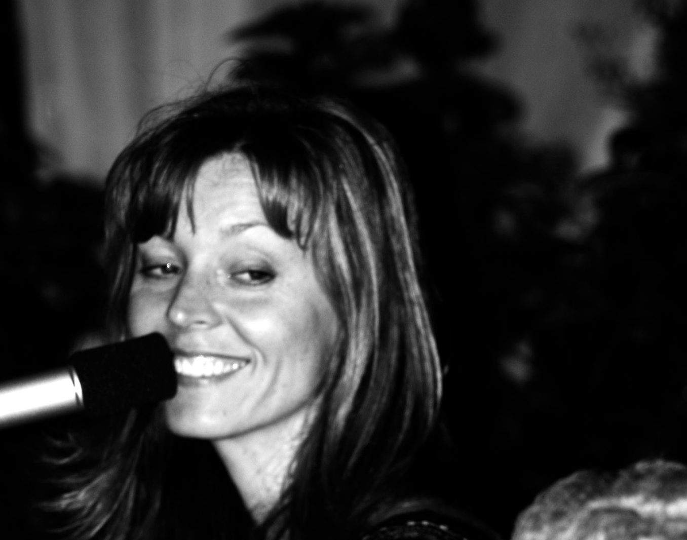 A black and white photo of a woman smiling into a microphone.