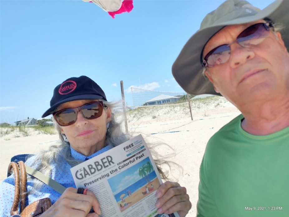 A man and woman in ball caps at a beach holding a Gabber Newspaper.