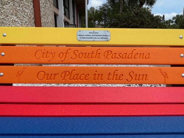 """A close up shot of a colorful bench with the words """"City of South Pasadena, Our Place in the Sun"""" engraved on it."""