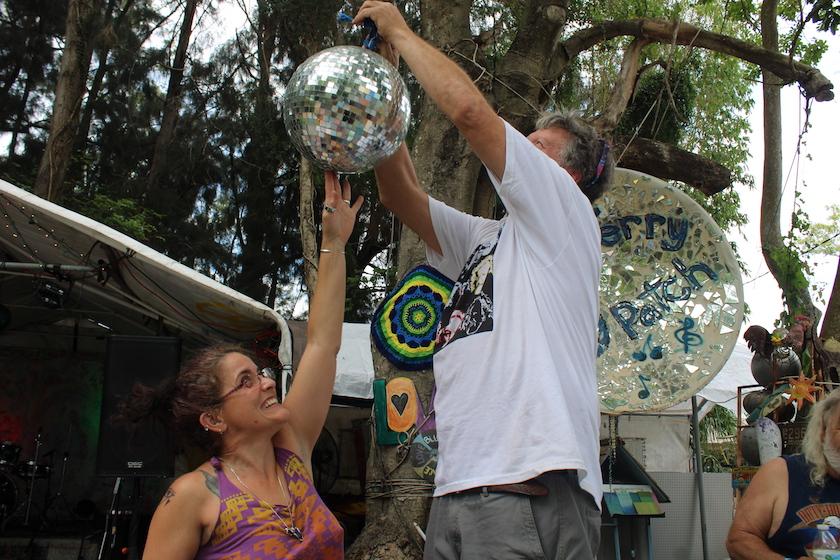 A woman helps a man in a white shirt hang a silver disco ball outside.